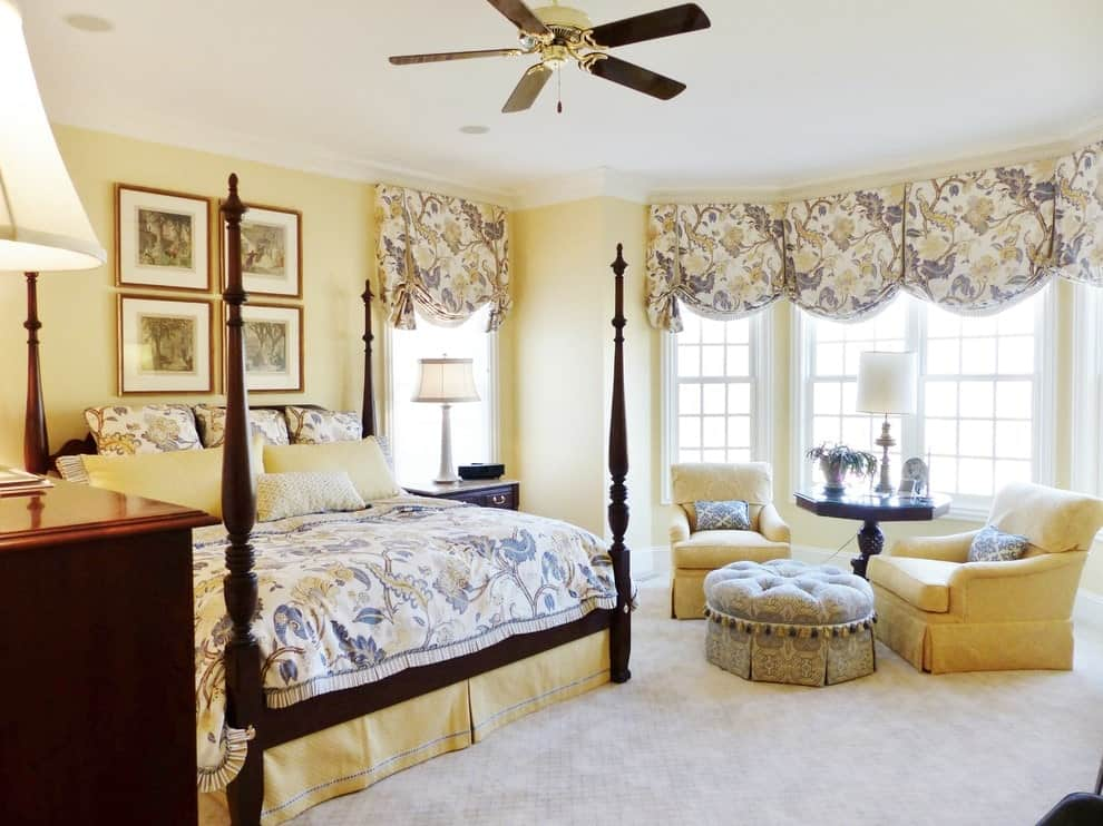 Lovely floral bedding matches the roman shades covering the white framed windows. This primary bedroom showcases a four-poster bed with gallery frames on top along with cozy seats over carpet flooring.