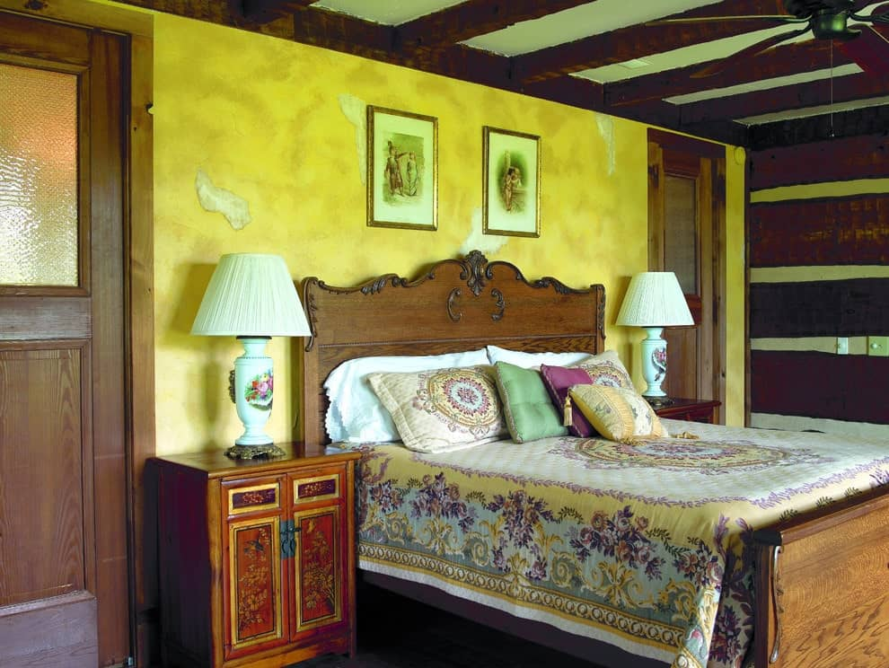 Brass framed artworks hang above the wooden bed that's dressed in floral bedding. It is flanked by lovely table lamps and nightstands against the distressed yellow wall.