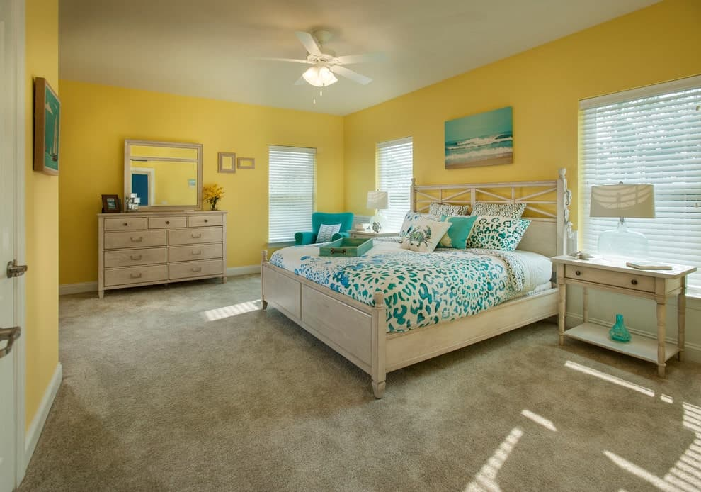 Yellow master bedroom with green accents from the artworks, tufted chair and printed bedding. It has a light wood dresser that matches the bed and nightstands topped with glass table lamps.