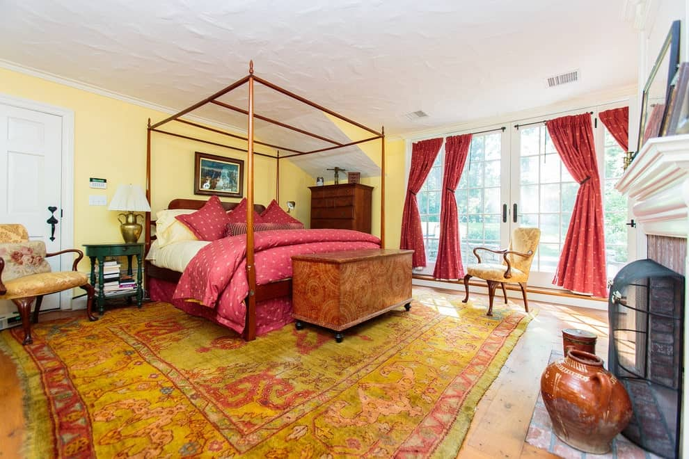 Yellow primary bedroom with wide plank flooring and French windows dressed in red dotted draperies. It includes a canopy bed and a fireplace enclosed in a wrought iron screen.