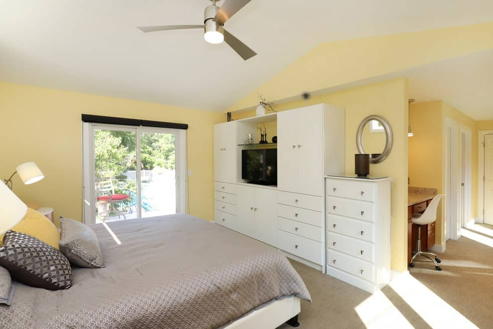 This primary bedroom is filled with white furniture and a chrome fan that hung from the vaulted ceiling. It has carpet flooring and glazed windows allowing natural light in.