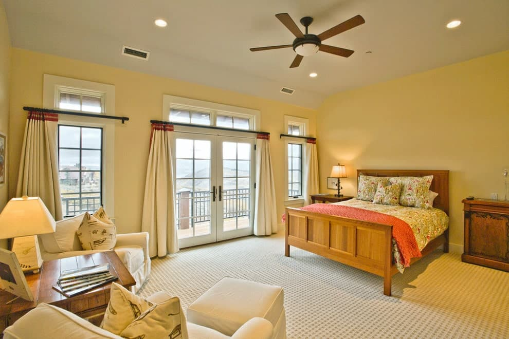 The yellow primary bedroom features a wooden bed that complements the nightstands and wood plank table flanked by white armchairs. It has carpet flooring and a French door leading out to the balcony with a breathtaking view.