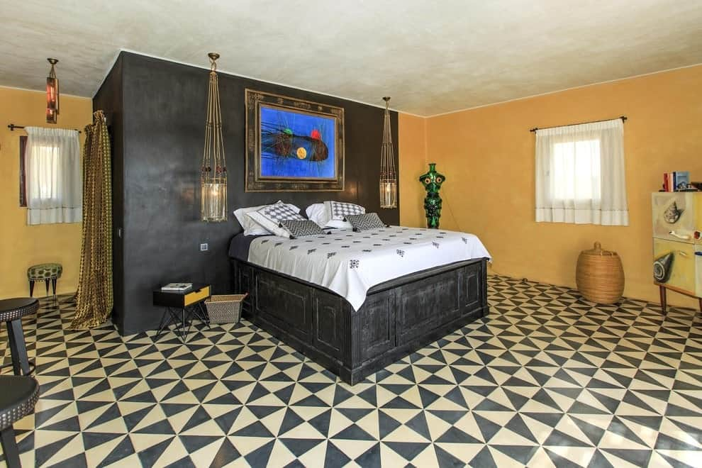 An eye-catching patterned flooring adds a striking accent in this yellow master bedroom boasting round seats and a black bed illuminated by glass pendant lights.