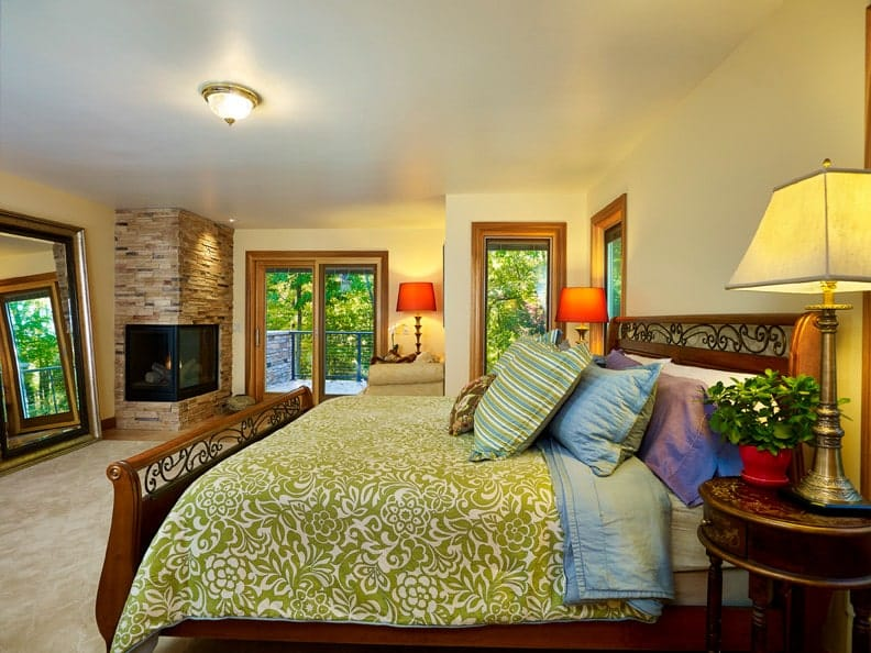 This primary bedroom showcases an ornate wooden bed wrapped in green floral duvet along with a double-sided fireplace that's fixed on the brick corner wall. It is illuminated by warm table lamps and a flush mount ceiling light.