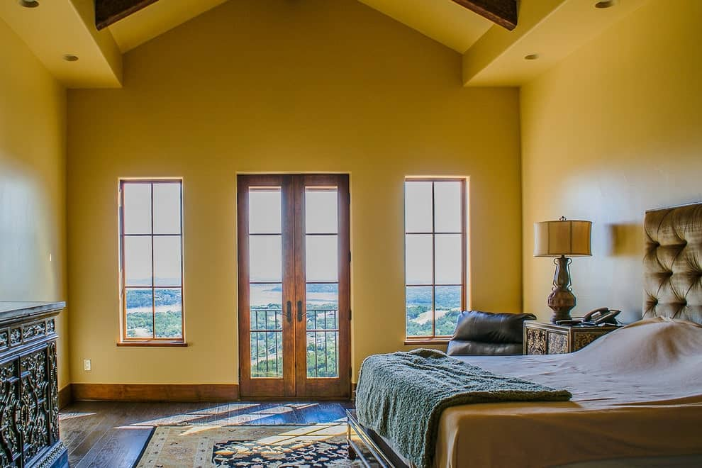 A carved wood cabinet faces the black floral rug and beige tufted bed in this primary bedroom with a cathedral ceiling and wooden framed windows and French door overlooking the outdoor scenery.