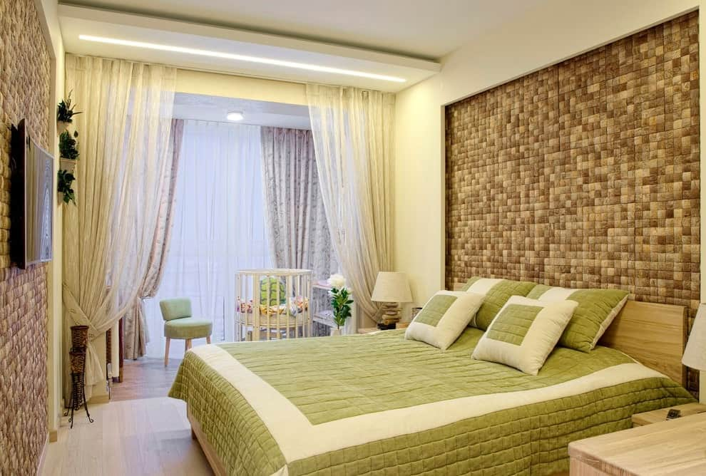 The contemporary primary bedroom offers a wall mount TV and a wooden bed dressed in green textured bedding. It is situated on an inset wall that's clad in beige textiles.