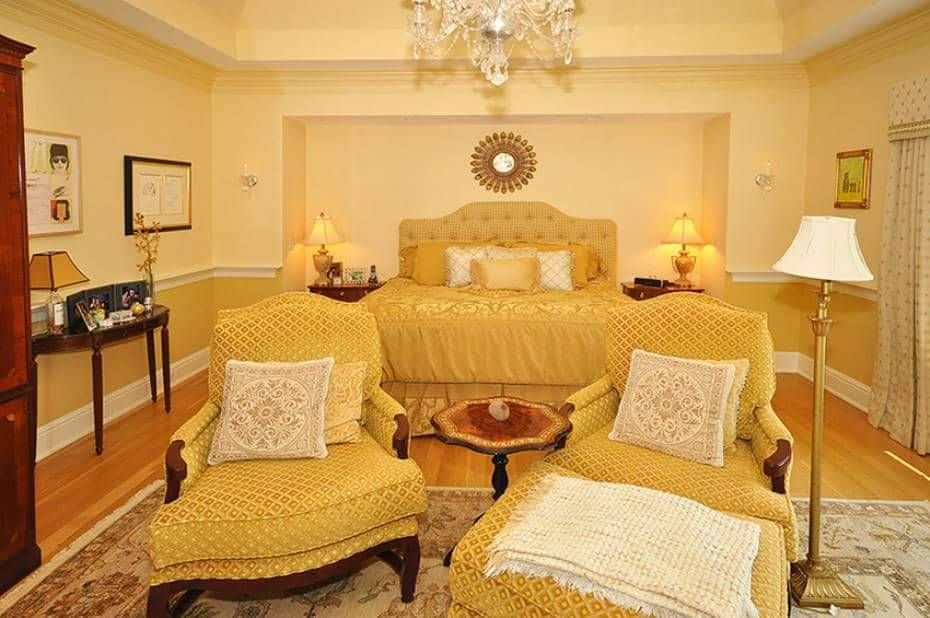 Yellow patterned chairs sit in front of the tufted bed that's flanked by wooden nightstands and traditional table lamps. This primary bedroom is decorated with a fancy crystal chandelier and a small sunburst mirror mounted on the inset wall.