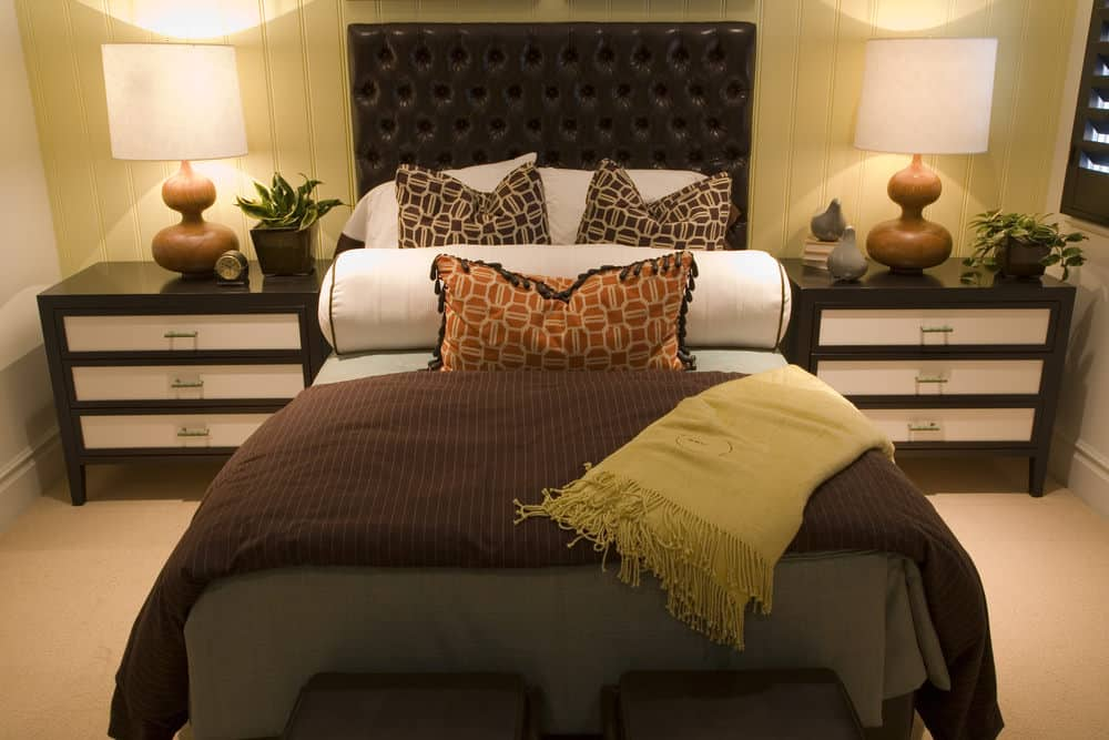 A closeup look at this master bedroom with a leather tufted bed in between dark wood nightstands that are topped with drum table lamps. It is placed against the light yellow beadboard wall and over carpet flooring.