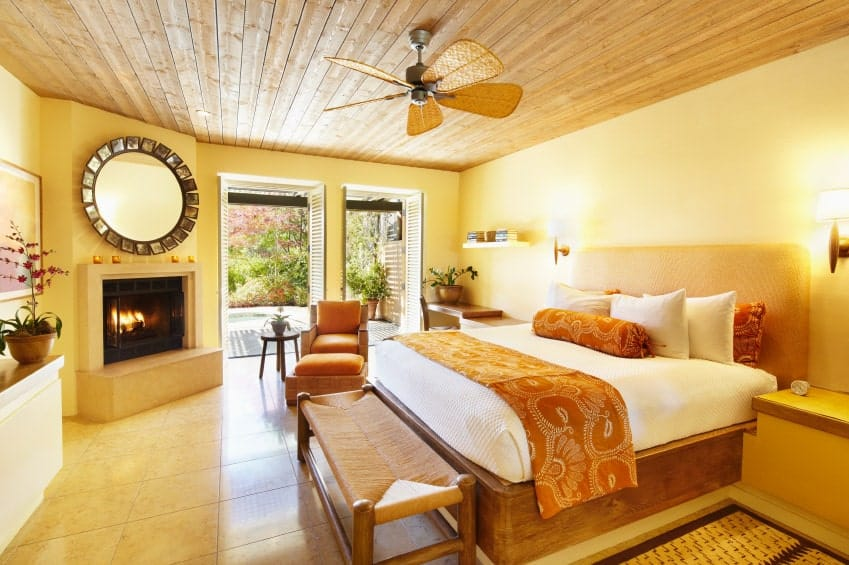 A large sunburst mirror hangs above the fireplace facing the comfy bed lighted by wall sconces. It is accompanied by a wooden bench and cushioned lounge chair over beige tiled flooring.