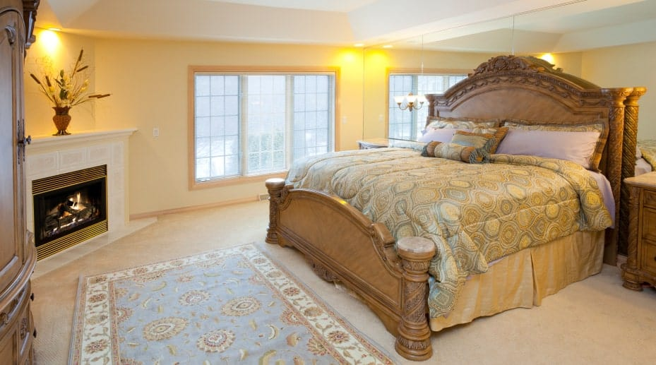 A corner fireplace with a lovely flower vase on top faces the elegant bed against the mirrored wall. This master bedroom showcases white framed windows and carpet flooring topped by a blue floral rug.