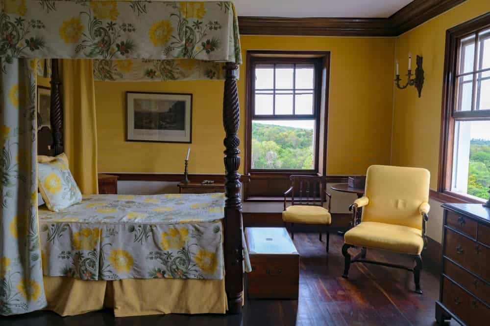 This primary bedroom features cushioned chairs and a lovely canopy bed dressed in yellow floral bedding. It has dark hardwood flooring and wooden framed windows inviting natural light in.