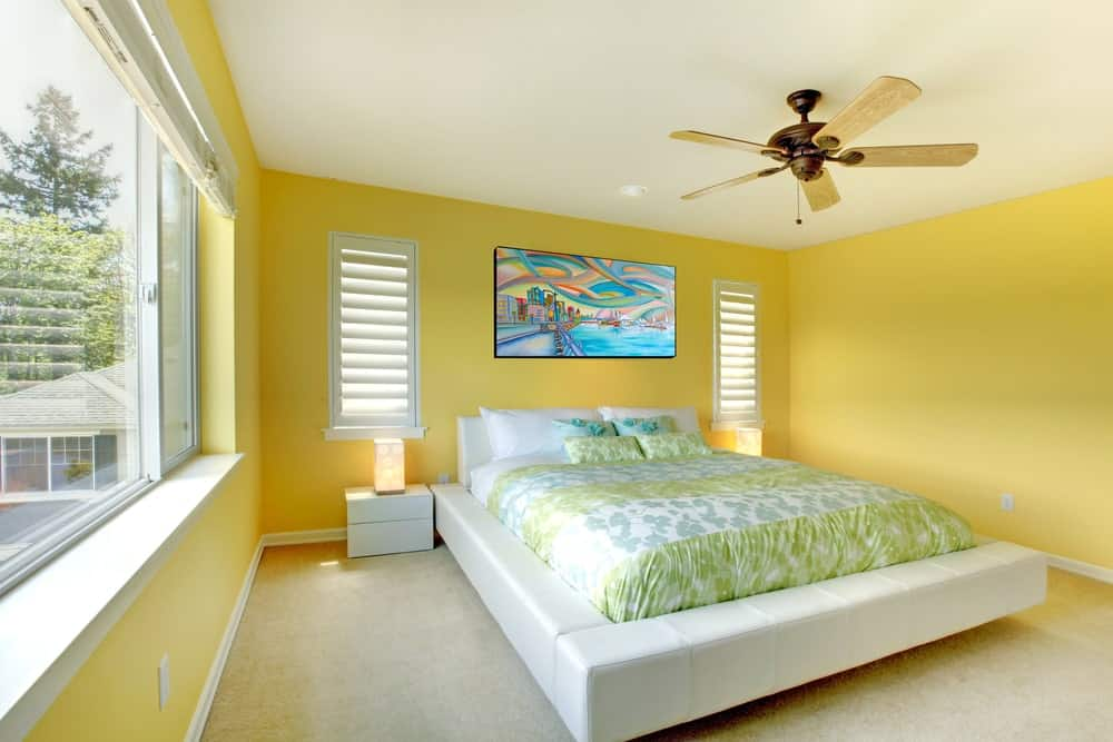 A bronze ceiling fan hangs over the white platform bed that's accented with colorful artwork. It is flanked by louvered windows and sleek nightstands over beige carpet flooring.