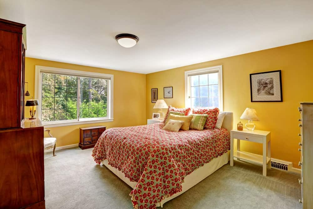Airy primary bedroom with a skirted bed and white nightstands topped with glass table lamps. It includes wooden cabinets and black-framed artworks mounted on the yellow walls.