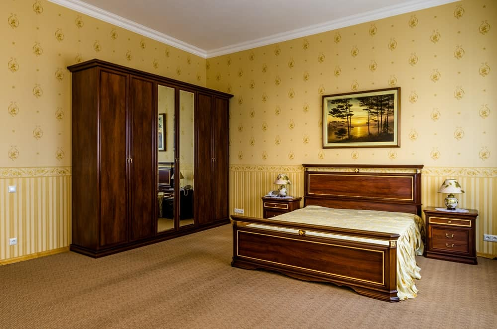 Clad in yellow patterned wallpaper, this primary bedroom features a dark wood wardrobe with full-length mirrors along with an elegant bed matching with wooden nightstands.