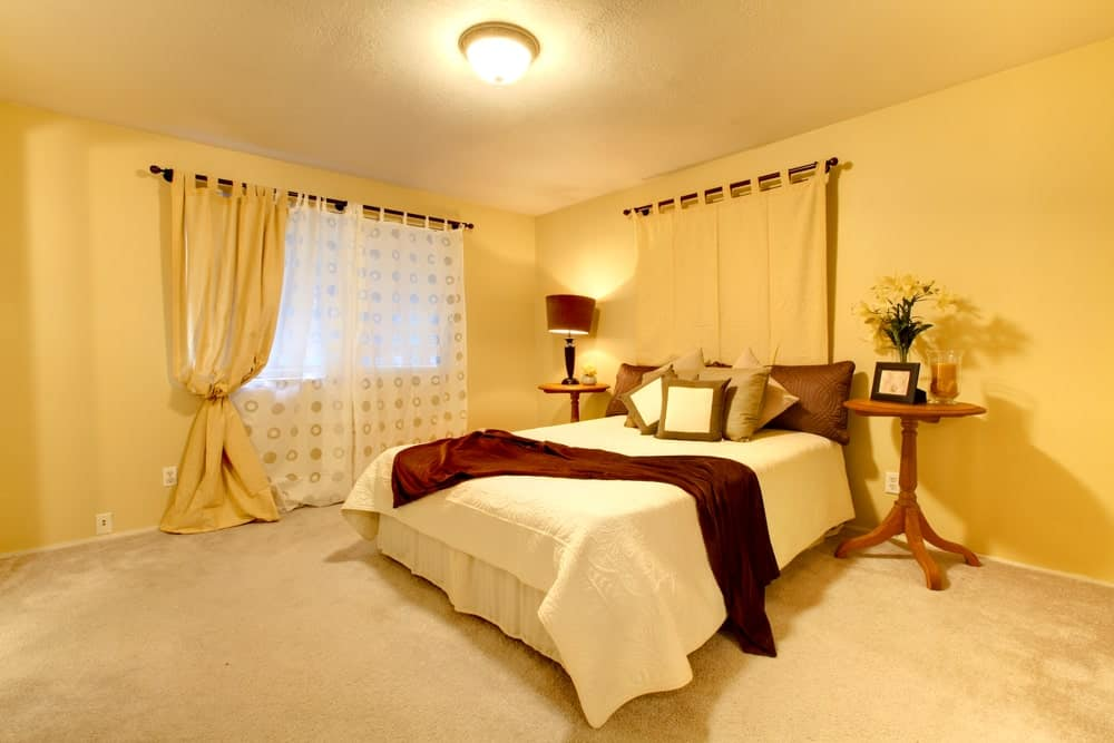 Well-lit master bedroom with beige carpet flooring and glazed windows covered in white sheer and yellow curtains. It includes round nightstands and a skirted bed illuminated by a flush mount light.
