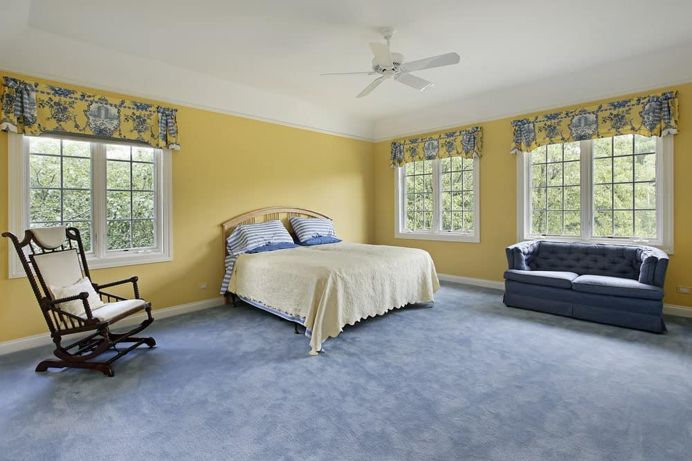 The spacious primary bedroom showcases a tufted sofa and a dark wood chair along with a wooden bed over gray carpet flooring. It is surrounded by yellow walls and white framed windows that are dressed in printed valances.