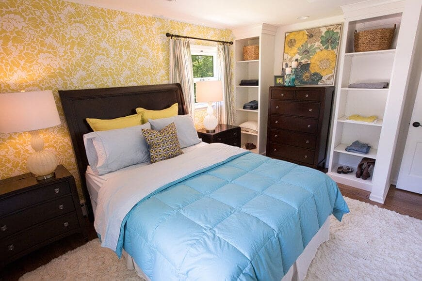 A floral artwork sits on a dark wood dresser matching with the nightstands that are topped with white table lamps. This primary bedroom offers built-in shelving and a skirted bed over a white shaggy rug.