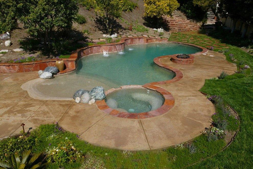 Freeform swimming pool with a hot tub and water features on the side. It is accompanied by a fire pit and an antique vase sitting next to the large rocks.