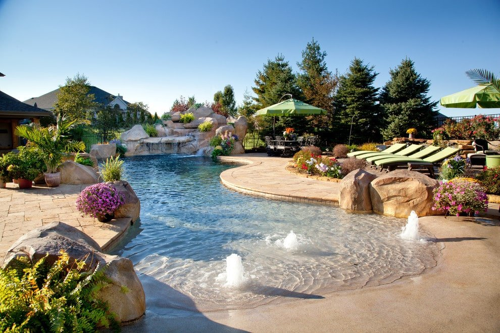 Boulder waterfall and pool bubblers are some of the highlights in this backyard pool with multiple seating and lovely flowers bringing a pop of colors in the area.