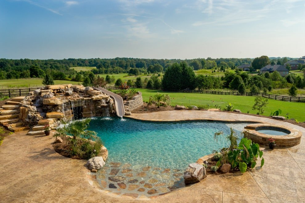 A backyard swimming pool with a serene ambiance overlooking an expansive view. It showcases a raised jacuzzi and a boulder waterfall that's integrated with a waterslide.
