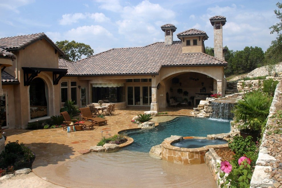 A Tuscan style house boasting a beach entry pool with a jacuzzi and a rock waterfall feature. It is accompanied by wicker seats and a white table.