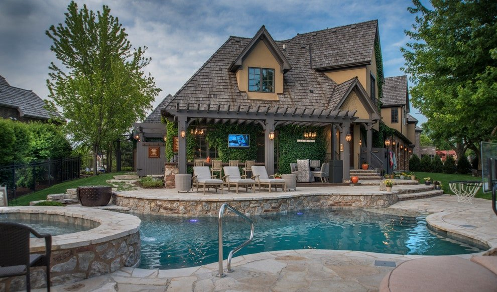 This house offers a freeform pool with a jacuzzi and a fire pit bowl that sits on the flagstone deck. It is complemented by gray cushioned loungers situated in front of the pergola bar.