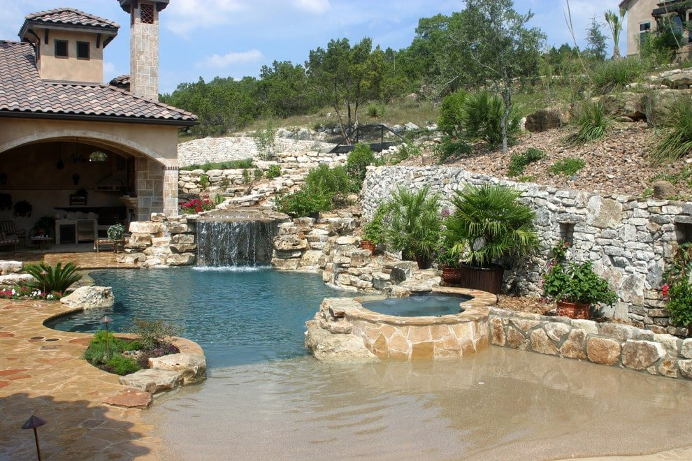 Grotto waterfall is the focal point in this beach entry pool with a raised jacuzzi that's clad in beige stone surround matching with the flagstone paving.