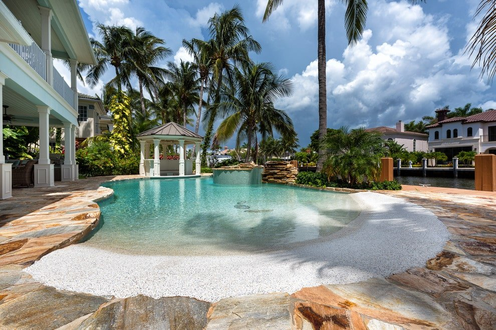 This two-story house features a zero-entry pool incorporated with a hot tub and a rock waterfall. It is complemented by a gazebo over the gorgeous stone deck.