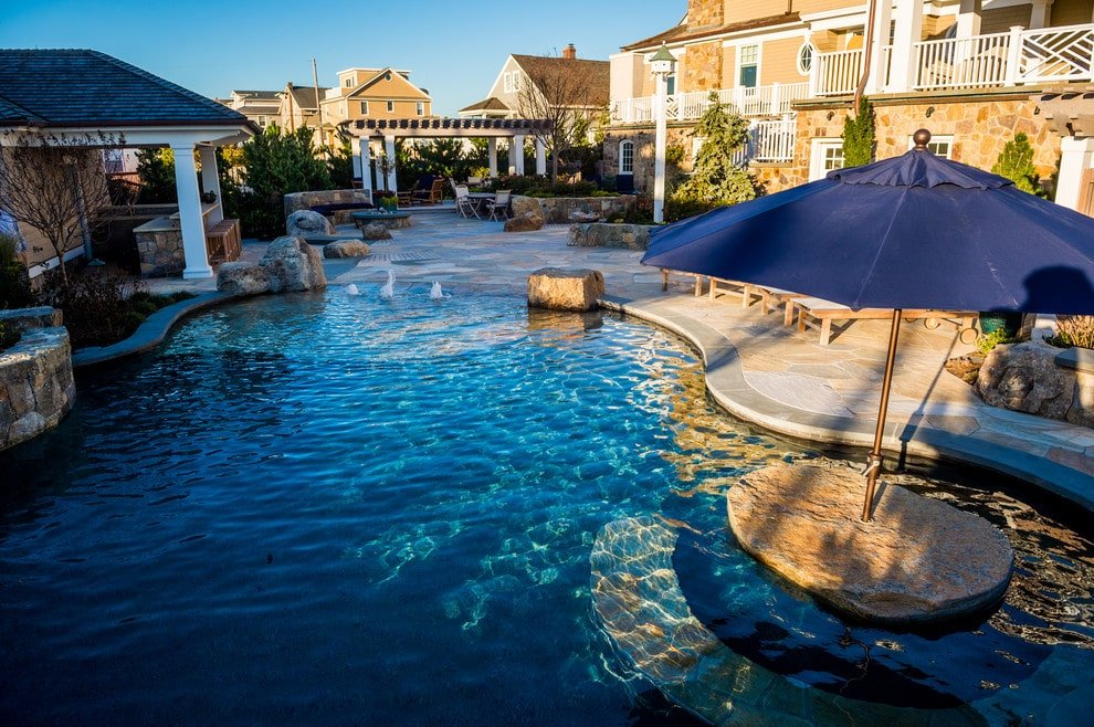 A resort-style backyard with a freeform swimming pool accompanied by a cabana and a firepit with a curved stone bench. There's a pergola at the far end that's filled with ample seating.