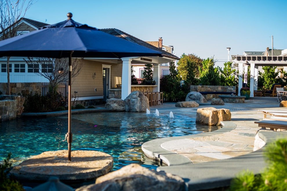 A blue umbrella adds shade in this sparkling swimming pool that's accented by large stones and pool bubblers. It offers multiple seating and a stone fire pit next to the pergola.