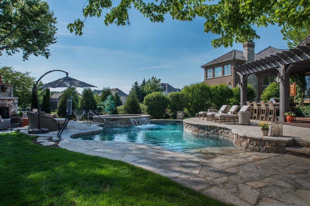 Tranquil swimming pool with a beach entry and a raised hot tub showcasing a water feature. It has a flagstone deck matching with the upper terrace that's filled with abundant seating and a pergola bar.