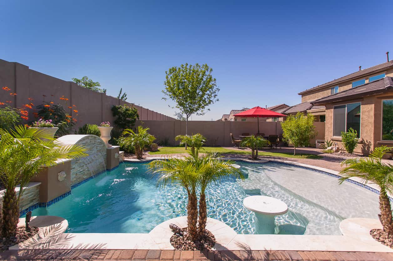 Beautiful palm trees surround this sparkling swimming pool boasting built-in round tables near the entry along with a waterfall feature on the side that's accented by large vases. Colorful flowers set a gorgeous backdrop highlighting the pool's features.