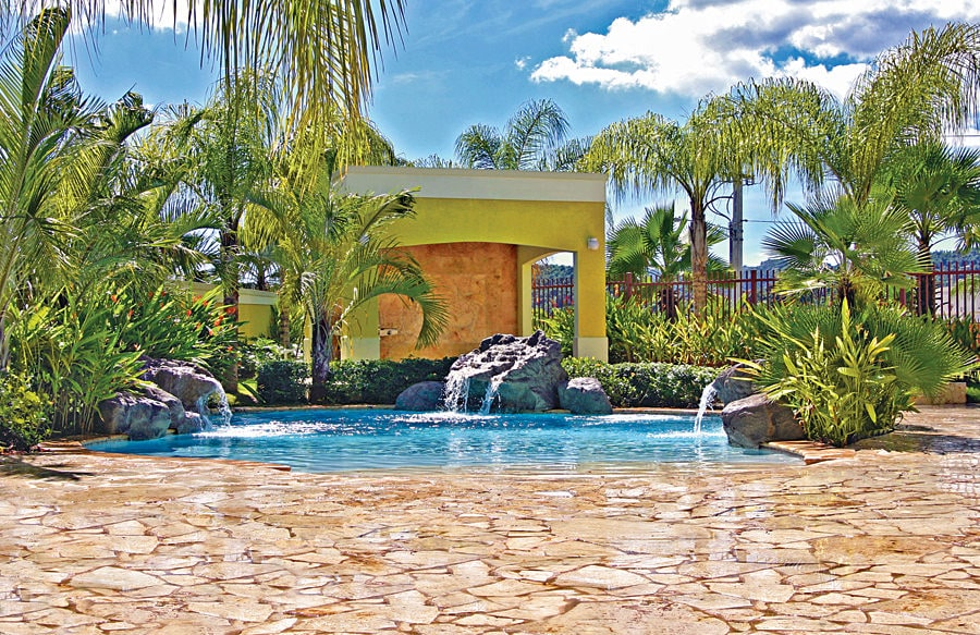 A small backyard pool surrounded by water features and lush green plants. It is completed with a flagstone deck and a sleek cabana painted in yellow.