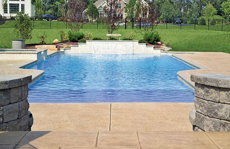 Modern swimming pool on an expansive lawn enclosed in a wrought iron fence. It boasts a water feature in front of the garden bed.