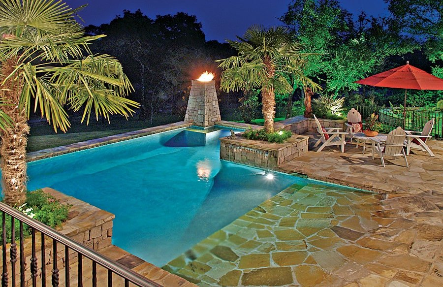 Backyard swimming pool with a flagstone deck and brick planters on the sides filled with palm trees. It includes a seating area and a torchlight accentuating the yard at night.