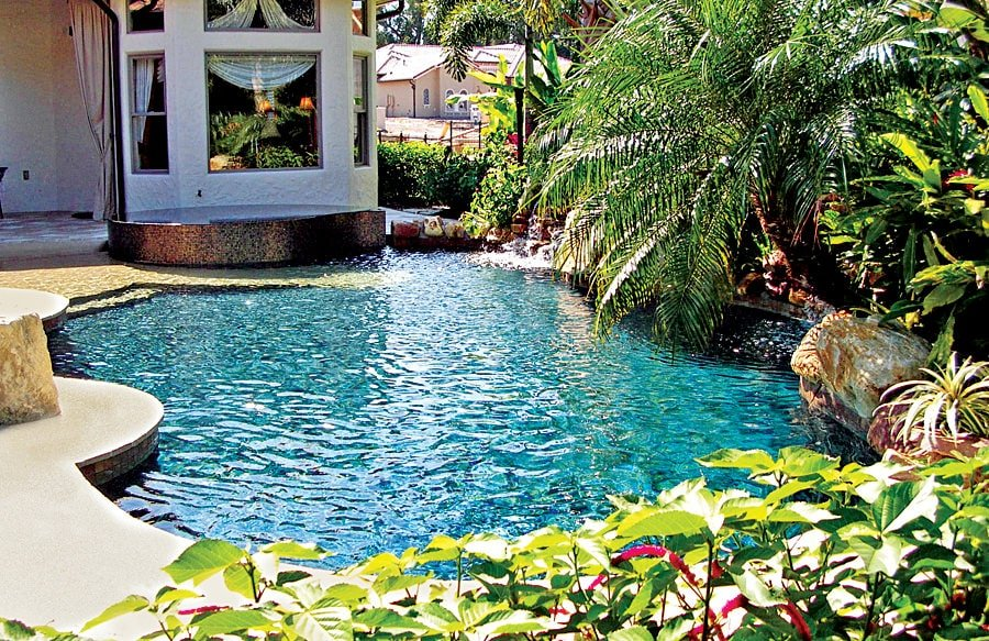 A sparkling swimming pool situated near the house. It is surrounded by luscious green plants and trees enhancing its beauty.