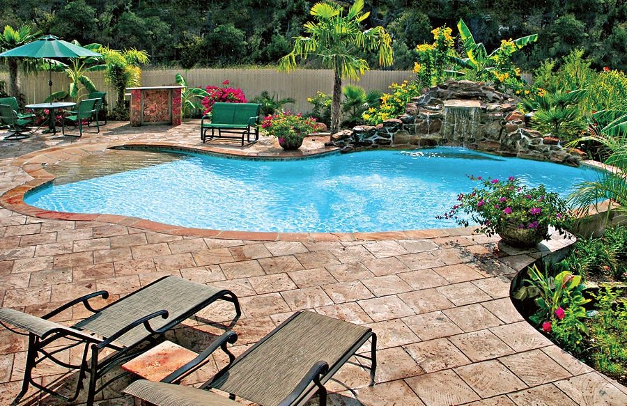 Backyard swimming pool enclosed in a wooden fence offering multiple seating and a bar over brick pavers. There's a gorgeous waterfall on the side that's accented by green plants and trees.