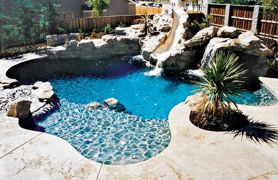 This backyard swimming pool is incorporated with a waterfall feature and a slide accented by large stones and subtle plants.