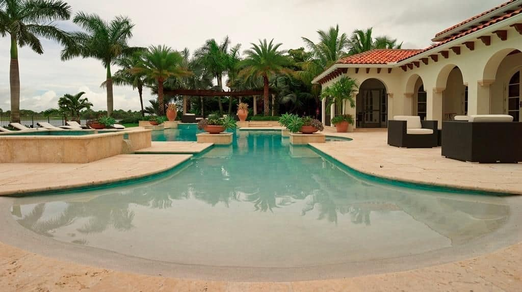 Mediterranean house with a beach entry pool surrounded by towering palm trees. It offers a pergola and plenty of white cushioned loungers.
