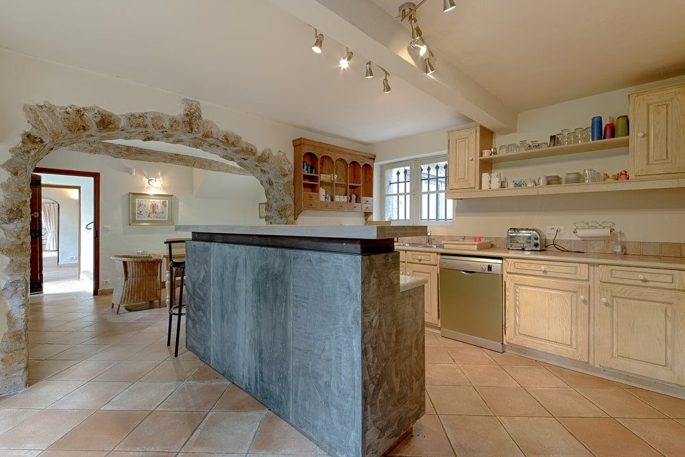 The kitchen has a tall kitchen island across from the beige cabinetry lining the walls. This matches with the ceiling that has a single exposed beam and modern lighting.