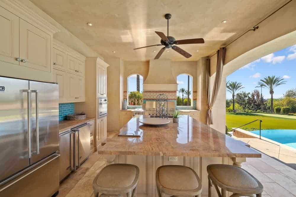 This is a close look at the full kitchen located in the cabana of the pool with stainless steel appliances and a large kitchen island that has a beige marble counter paired with stools. These are then complemented by an open wall that brings in natural light.
