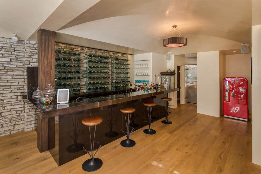 Take a look at the home's bar area featuring multiple wine racks and a bar island with classy bar stools. Images courtesy of Toptenrealestatedeals.com.
