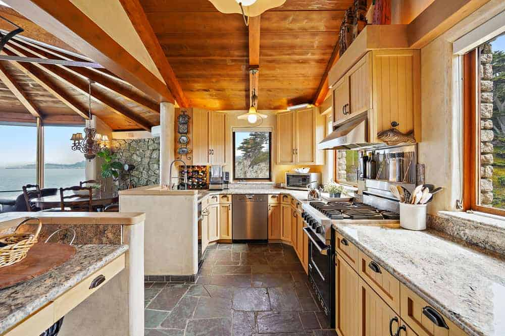 Through the entry on the side of the dining area is the long and narrow kitchen with wooden cabinetry lining the walls that matches the wooden beamed ceiling topped with gray marble.