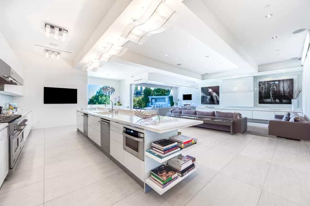 This is a closer look of the kitchen with a large kitchen island that houses stainless steel appliances topped with white counters and decorative lighting above from the white ceiling.
