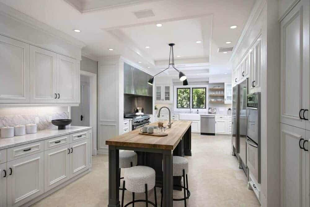 The bright kitchen has white shaker cabinets lining the walls surrounding a large kitchen island with butcher clock counter topped with a modern lighting hanging from the coffered ceiling.