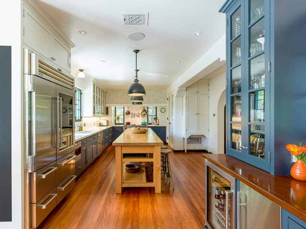 This is the kitchen that has a large wooden kitchen island in the middle topped with pendant lights and paired with wooden stools.