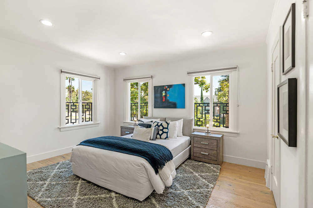This bedroom offers a nice comfy bed with two bedside tables. The room features white walls, glass windows and hardwood flooring. Images courtesy of Toptenrealestatedeals.com.