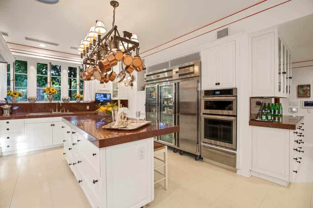 The large chef's kitchen has dark brown counters and backsplash that contrast the bright white cabinetry of the walls and kitchen island. These also make the stainless steel modern appliances stand out.