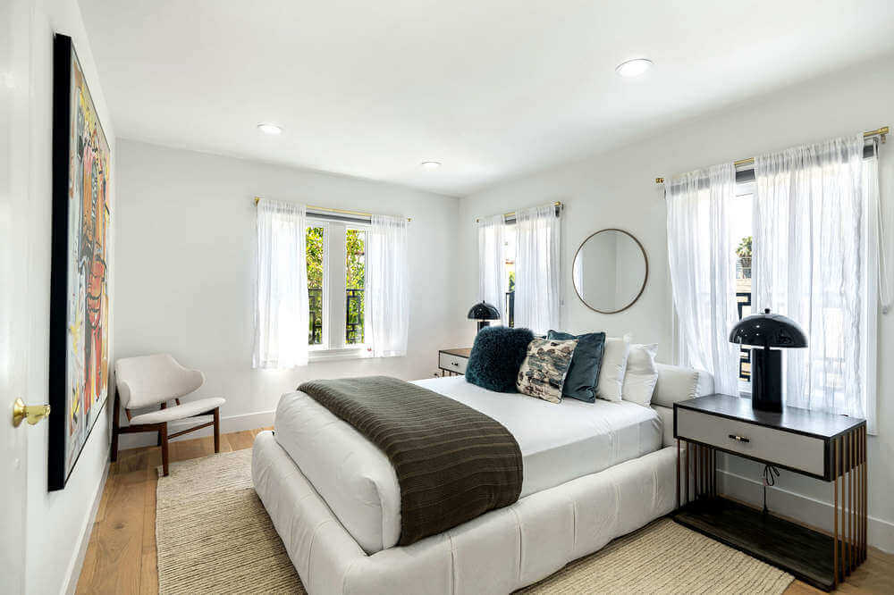 This bedroom offers a white modern bed with stylish table lamps on both sides. The wall in front features a large wall decor. Images courtesy of Toptenrealestatedeals.com.