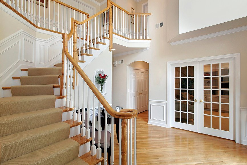 A closer look at this home's 180 degree turn staircase with white railings, wooden handrails and carpeted steps.